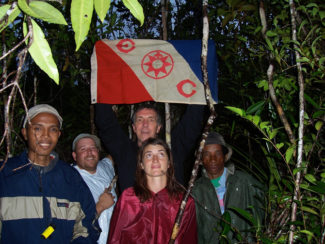 Photo of Lin Lougheed, center holding Explorers Club flag, with American and Madagascar team.