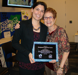 Photo of Tracy Magellan receiving the award from Ossie Hanauer